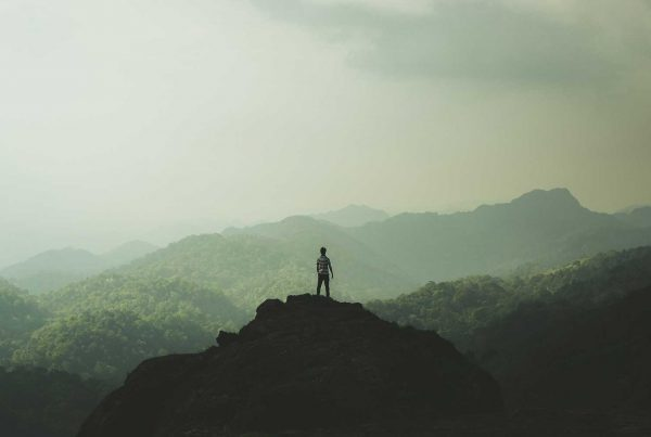Guy standing on top of mountain