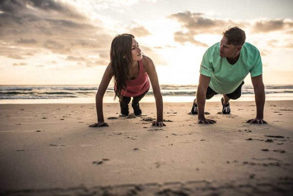 couple doing push up at the beach
